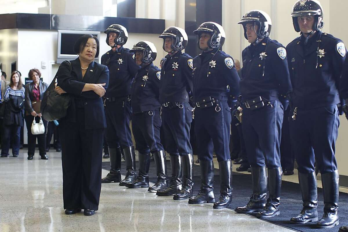 Oakland Mayor Jean Quan watches as members of the Oakland police department stand at attention during a I-580 freeway sign dedication ceremony in honor of fallen officers Sgt. Mark Dunakin, Sgt. Ervin Romans, Sgt. Daniel Sakai and Officer John Hege who died on duty in 2009 at the Police Administrative Building in Oakland, Calif. on Wednesday, March 21, 2012.