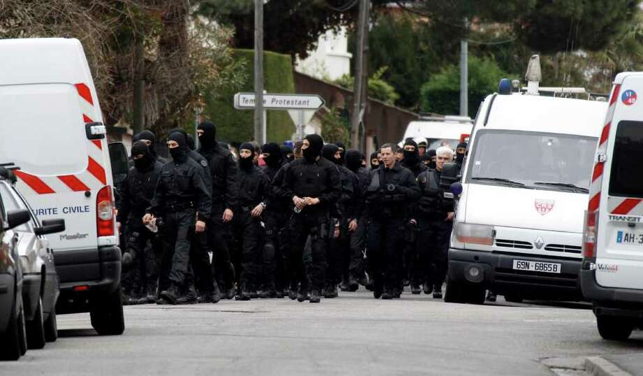 French police officers leave the area where an Islamic extremist died after jumping from his window, gun in hand, in a fierce shootout with police, in Toulouse, France, Thursday. The death of Mohamed Merah, 23, ended a more than 32-hour standoff with an elite police squad trying to capture him alive. Merah was wanted in the deaths of seven people, three paratroopers, three Jewish schoolchildren and a rabbi, all killed over a period of 10 days. (AP Photo/Bob Edme) Photo: Bob Edme, ASSOCIATED PRESS / AP2012