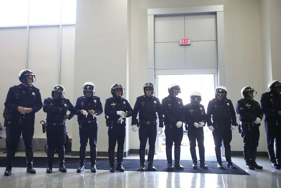 Members of the Oakland police color guard line up Wednesday at police headquarters for a ceremony renaming the Keller Avenue bridge across Interstate 580 for the four officers slain on March 21, 2009. At right, an officer stands at attention behind a photograph of Officer John Hege and Sgt. Mark Dunakin, slain during a traffic stop. SWAT Sgts. Ervin Romans and Daniel Sakai died later in a shootout. Photo: Stephen Lam, Special To The Chronicle