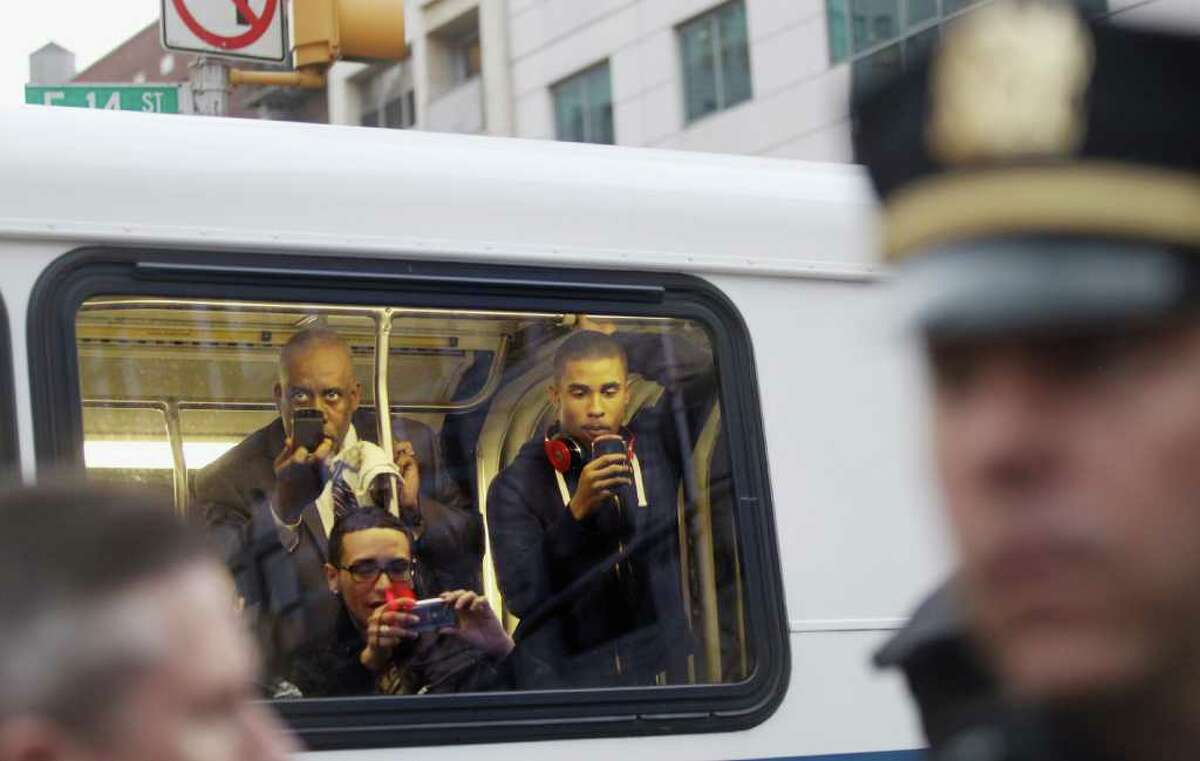 NEW YORK, NY - MARCH 21: People on a bus take photos as supporters of Trayvon Martin march past while blocking traffic during a