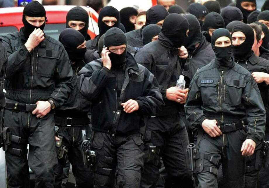 "French members of the RAID special police forces unit leave after the assault on the besieged flat of self-professed Al-Qaeda militant Mohamed Merah, on March 22, 2012 in Toulouse, southwestern France. Mohamed Merah died in the assault and ""jumped from the window still shooting,"" Interior Minister Claude Gueant told journalists, adding that Merah had attacked police ""with extreme violence"" after bursting out of the bathroom. AFP PHOTO / PASCAL PAVANI Photo: PASCAL PAVANI, AFP/Getty Images / AFP"
