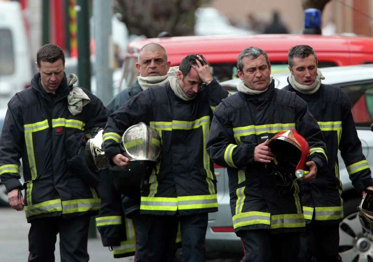 French firefighters leave after a police assault on a suspected Islamic extremist holed up in an apartment in Toulouse, southwestern France, Thursday, March 22, 2012. Mohamed Merah, who boasted of killing seven people to strike back at France died Thursday after jumping from his window, gun in hand, in a fierce shootout with police, a French minister said..