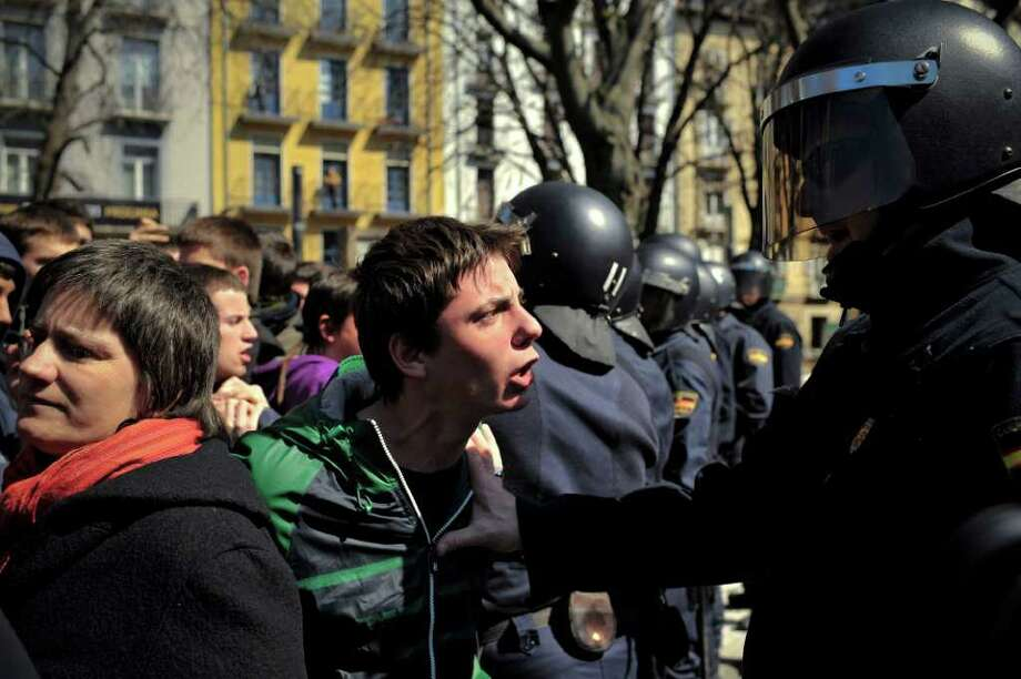 Spanish students shout slogans at a police officer during a march to protest against the government's tough new labor reforms and cutbacks planned by the conservative Popular Party of Spanish Prime Minister Mariano Rajoy, in Pamplona, northern Spain, Thursday, March 22, 2012. (AP Photo/Alvaro Barrientos) Photo: Alvaro Barrientos, Associated Press / AP