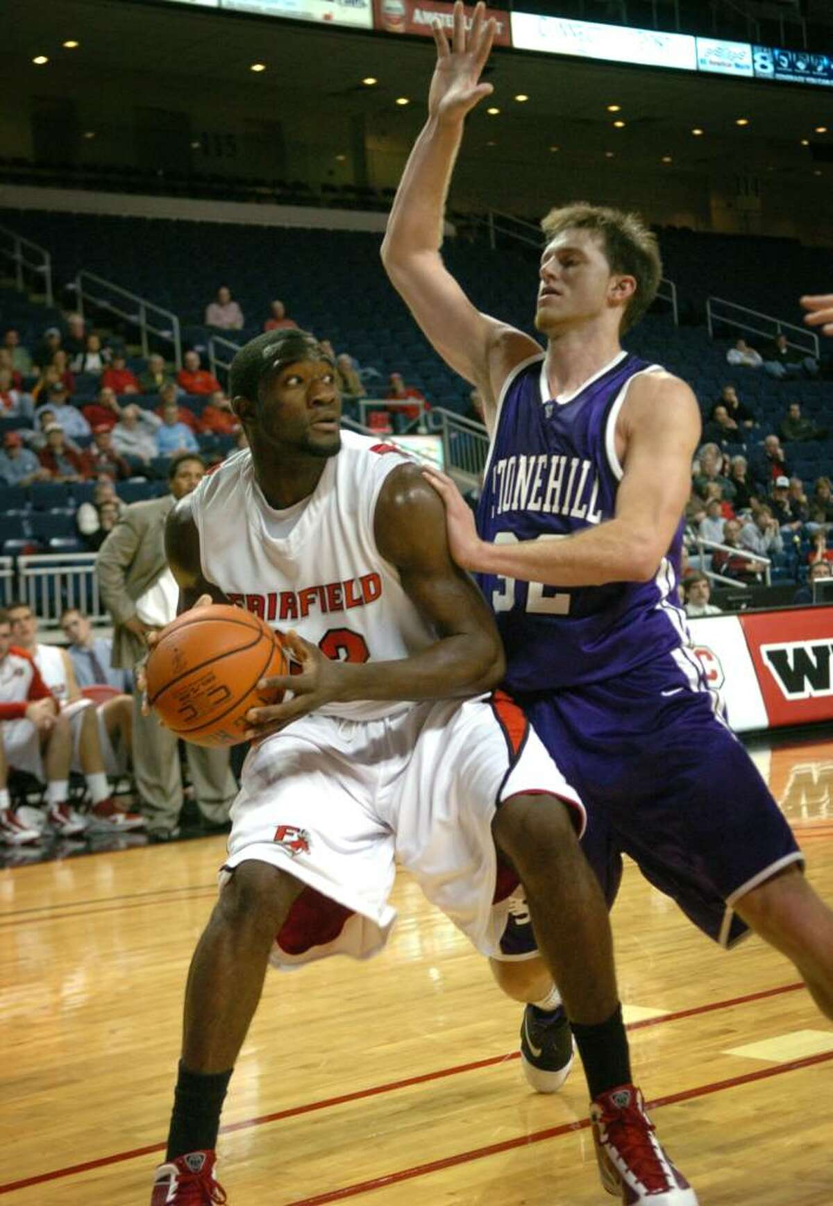 Fairfield's Anthony Johnson looks to score down low against Stonehill defender A.J. Rudowitz during a recent game at the Arena at Harbor Yard in Bridgeport.