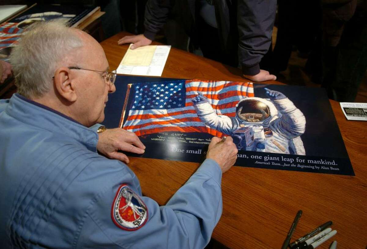 Alan Bean signs a poster of one of his paintings at the Greenwich Gallery Workshop in Seymour, Conn., on Nov. 14, 2009. Bean visited the gallery on the 40th anniversary to the day of his launch to the moon. Bean was the fourth human to ever walk on the surface of the moon.