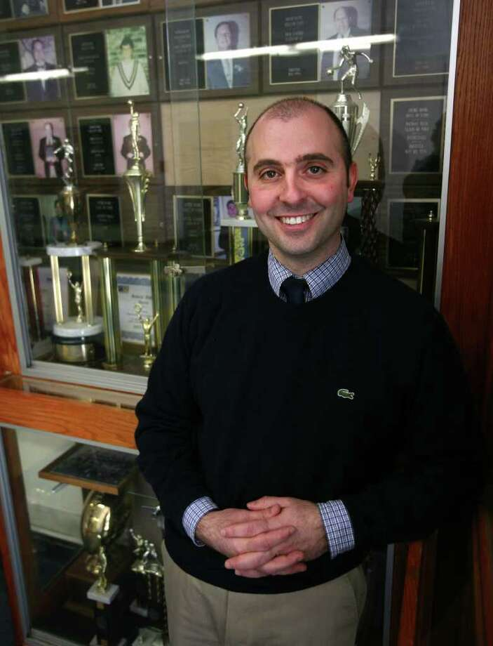 Notre Dame of Fairfield High School Athletic Director Rob Bleggi stands in front of the school's wall of fame trophy case on Tuesday, March 6, 2012. Photo: Brian A. Pounds / Connecticut Post