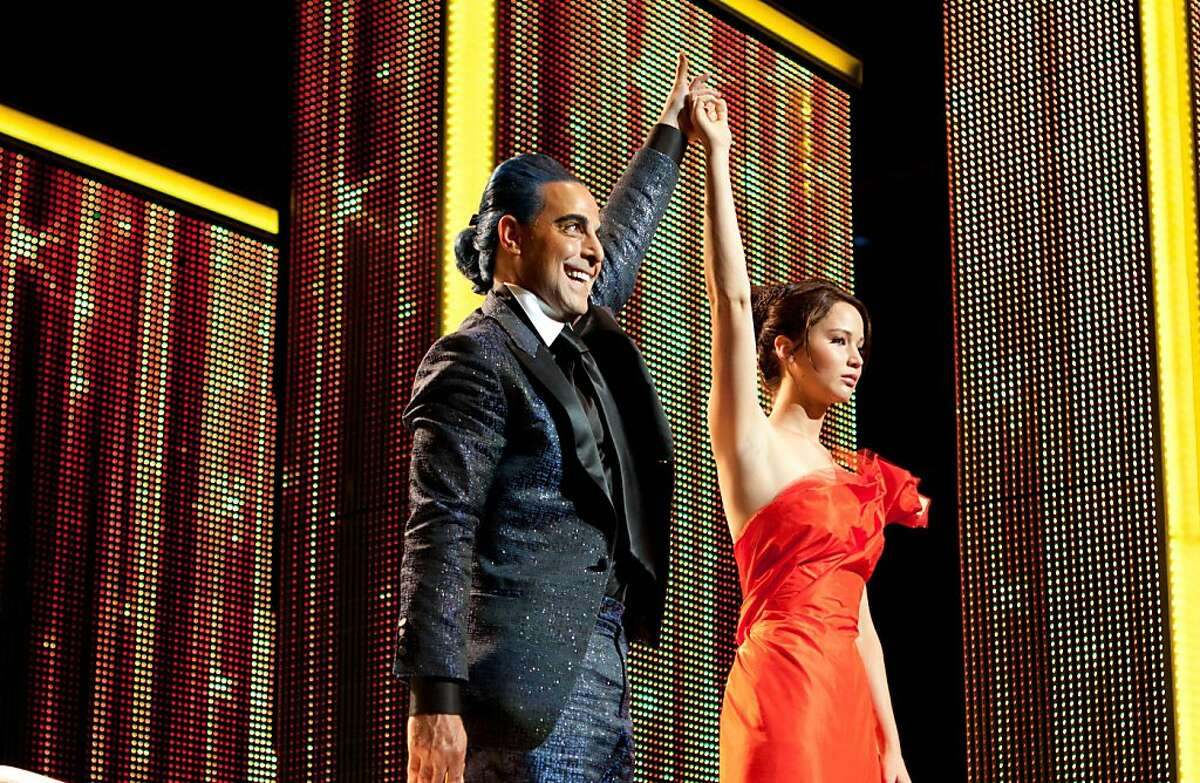 Caesar Flickerman (Stanley Tucci, left) and Katniss Everdeen (Jennifer Lawrence) star in