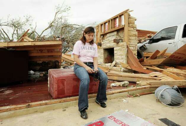 Josie Juarez sits in the ruins of her Devine home, destroyed when a tornado touched down earlier in the week. Juarez's 15-year-old daughter, Jessi, who was the only person home when the tornado hit, survived by taking shelter in the bathroom. Photo: Darren Abate, Associated Press