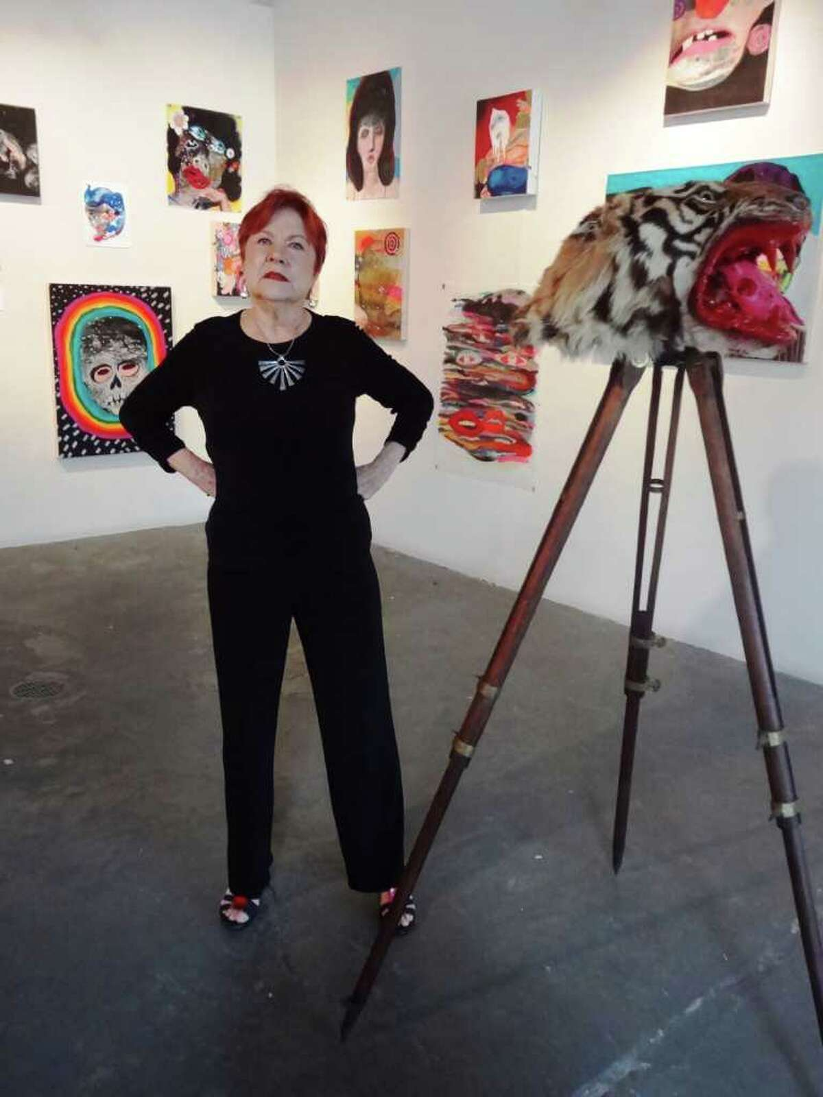 Joan Grona stands in her Blue Star arts complex gallery with paintings by Linda Arredondo and sculpture by S.C. Giesey III.