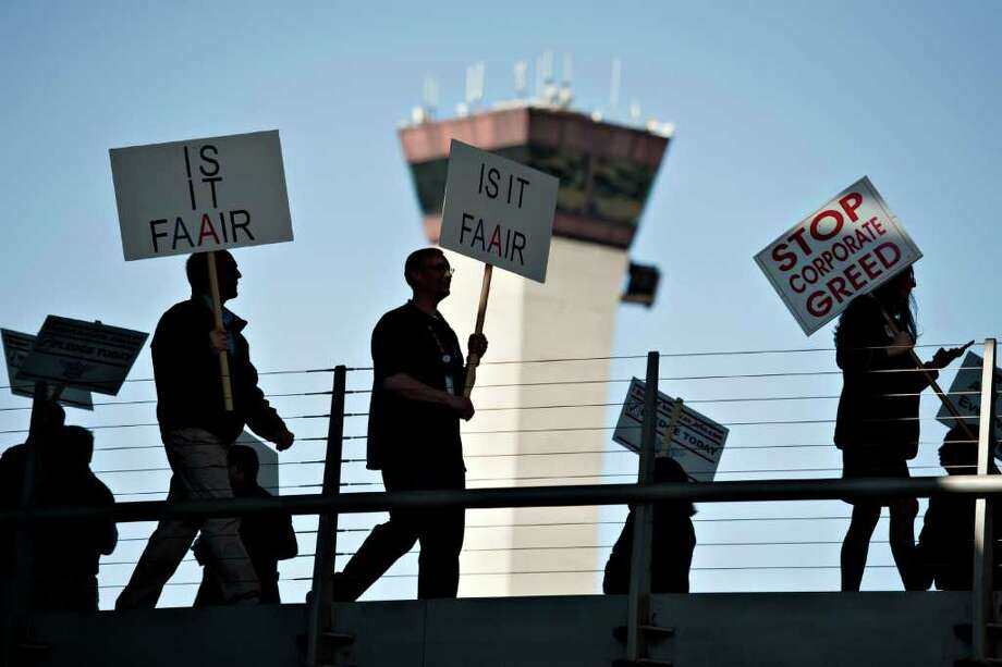 An airport control tower stands in the background as members of Transportation Workers Union Local 521 demonstrate outside American Airlines Terminal 3 at O'Hare International Airport in Chicago, Illinois, U.S., on Wednesday, Feb. 29, 2012. The group was demonstrating against proposed layoffs associated with the bankruptcy of American Airlines parent AMR Corp. Photographer: Daniel Acker/Bloomberg Photo: Daniel Acker / © 2012 Bloomberg Finance LP