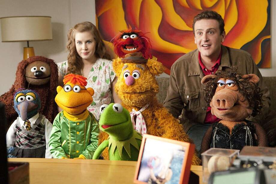 "In this film publicity image released by Disney, Amy Adams, left, and Jason Segel are shown with the muppet characters in a scene from ""The Muppets."" (AP Photo/Disney Enterprises, Patrick Wymore) Photo: Patrick Wymore, Associated Press"