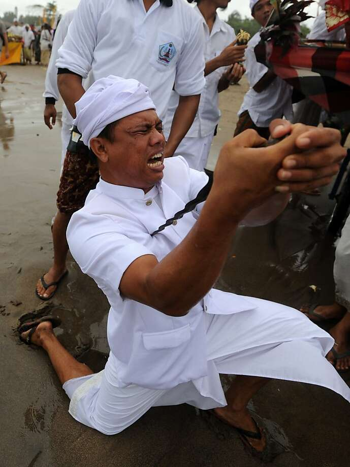 "A Balinese in a trance stabs himself with a ""keris"", a traditional dagger, while he and fellow Balinese attend the Melasti ceremony prayer at Petitenget beach in Kuta on the island of Bali on March 20, 2012.  Melasti is a purification festival which is held three days before Nyepi, a day in silent, as during the Nyepi day Hindus on the island of Bali are not allowed to work, travel or take part in any indulgence. Photo: Sonny Tumbelaka, AFP/Getty Images"