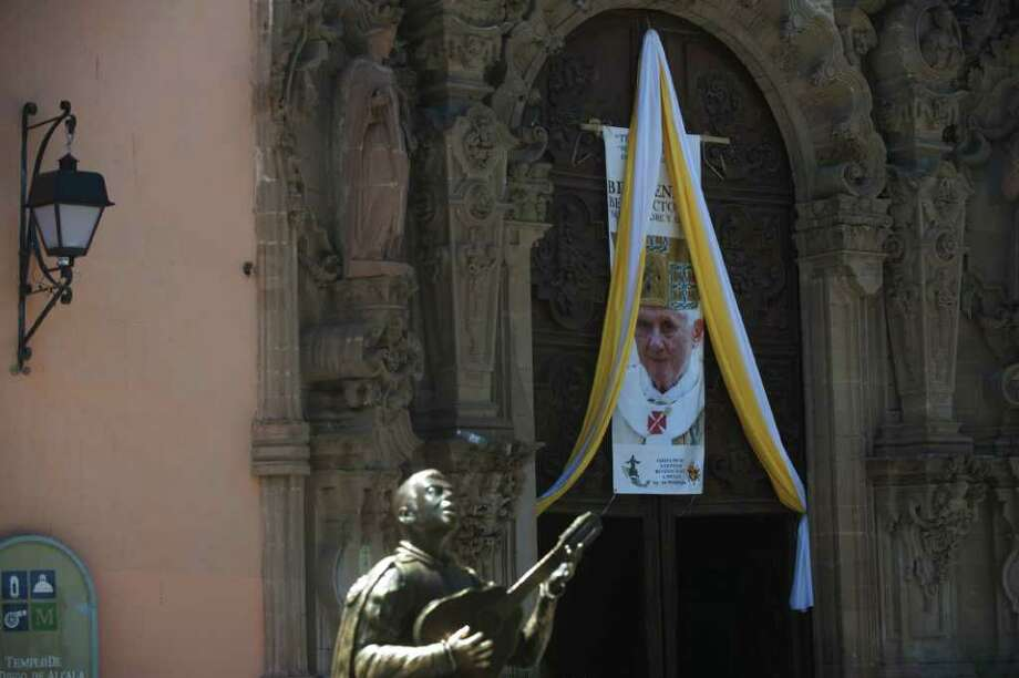 An image of Pope Benedict XVI and framed by the colours of the Vatican hungs from the entrance dorr of the Saint Diego de Alcala Church in Guanajuato, Mexico on March 22, 2012. Pope Benedict XVI will visit Mexico between March 23 and 26 on his first visit to the country. Photo: YURI CORTEZ, AFP/Getty Images / AFP