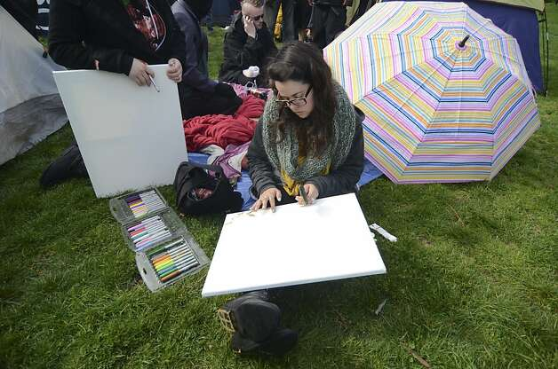 Protester Gricelda Gutierrez paints a canvas at the camp. After two nights of camping out at Mosswood Park, Occupy protesters announced their presence via Twitter, dubbing the camp Wall Street West and referring to the park as Huey P. Newton Park. Police arrived around 11 AM, forcing protesters to dismantle the eight tents that had been erected by that point. There were no arrests. Photo: Skyler Reid, Special To The Chronicle
