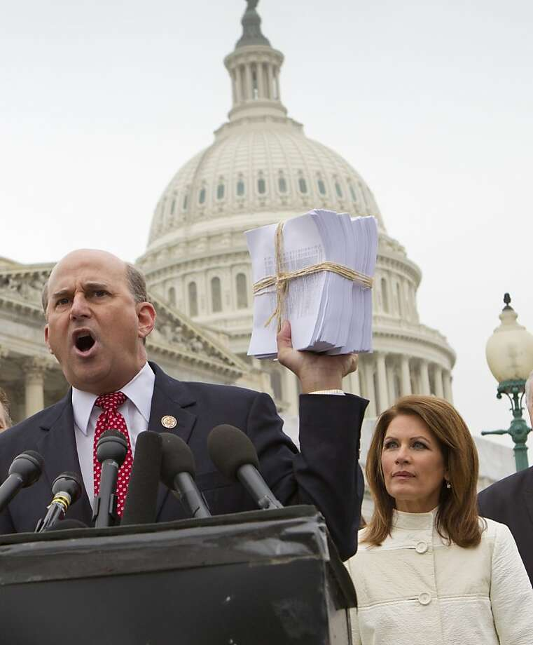 Rep. Louie Gohmert, R-Texas, accompanied by Rep. Michele Bachmann, R-Minn., holds up a copy of the Patient Protection and Affordable Care Act, often referred to as Obamacare, during a a news conference on Capitol  Hill in Washington, Wednesday, March 21, 2012, to express their anger about the legislation on the second anniversary of its passage. (AP Photo/J. Scott Applewhite) Photo: J. Scott Applewhite, Associated Press