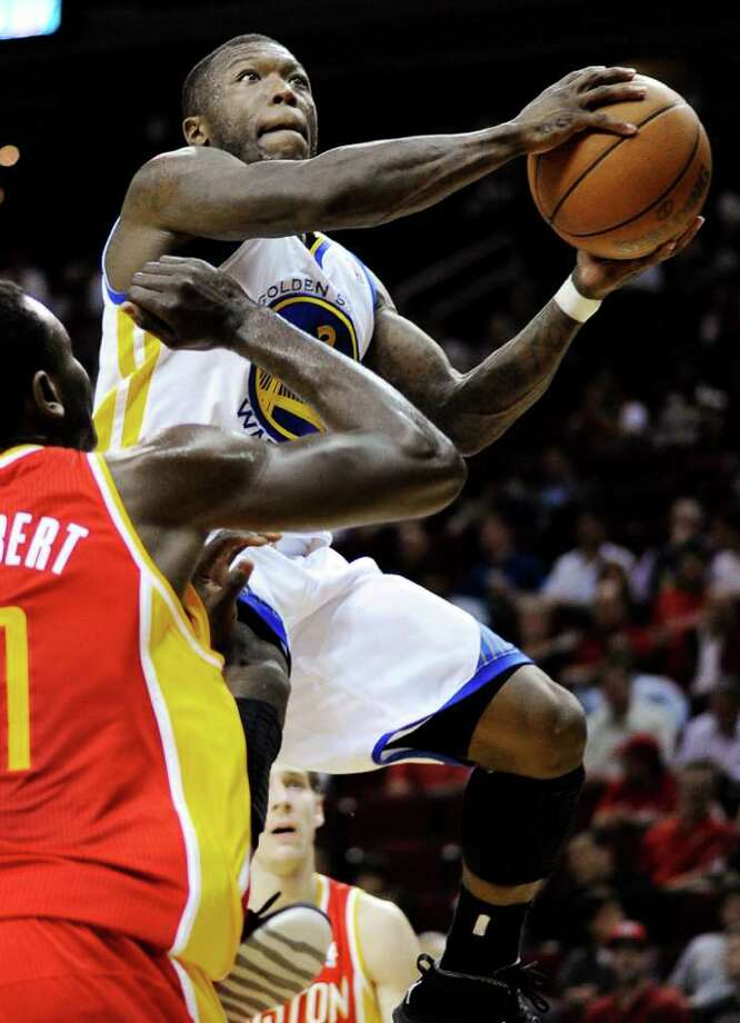 Golden State Warriors' Nate Robinson, right, shoots past Houston Rockets' Samuel Dalembert in the first half of an NBA basketball game, Thursday, March 22, 2012, in Houston. (AP Photo/Pat Sullivan) Photo: Pat Sullivan, Associated Press / AP