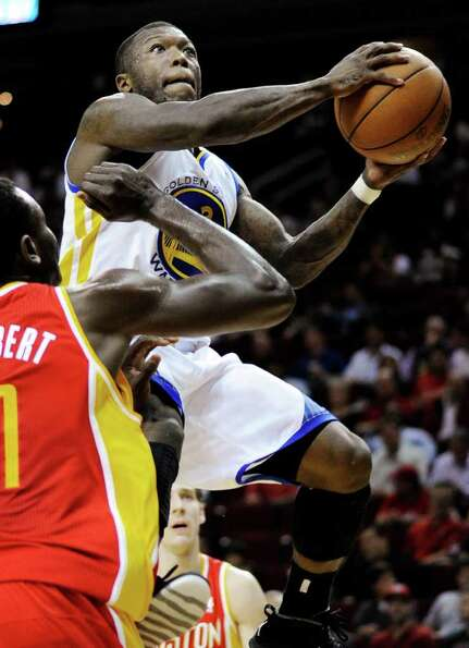 Golden State Warriors' Nate Robinson, right, shoots past Houston Rockets' Samuel Dalembert in the fi