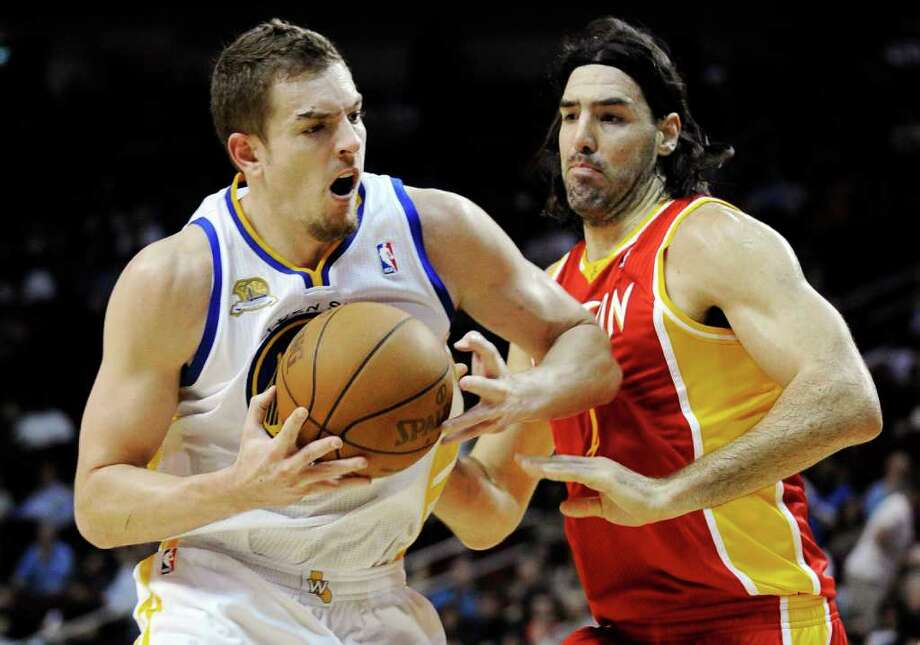 Golden State Warriors' David Lee, left, drives against Houston Rockets' Luis Scola in the first half of an NBA basketball game, Thursday, March 22, 2012, in Houston. (AP Photo/Pat Sullivan) Photo: Pat Sullivan, Associated Press / AP