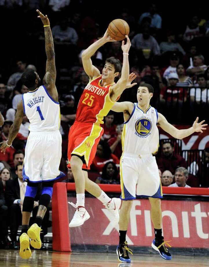 Houston Rockets' Chandler Parsons (25) passes the ball between Golden State Warriors' Dorell Wright (1) and Klay Thompson (11) in the first half of an NBA basketball game, Thursday, March 22, 2012, in Houston. (AP Photo/Pat Sullivan) Photo: Pat Sullivan, Associated Press / AP