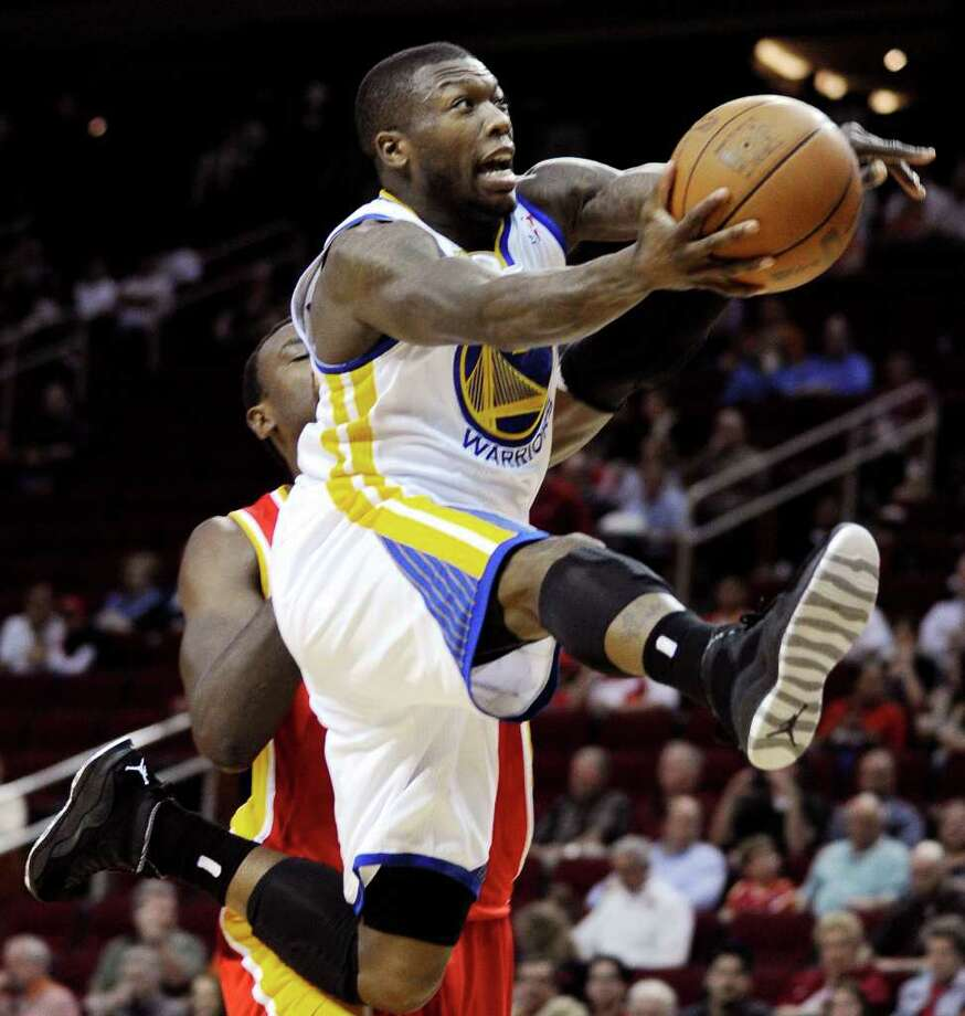 Golden State Warriors' Nate Robinson, top, goes to the basket in the first half of an NBA basketball game against the Houston Rockets, Thursday, March 22, 2012, in Houston. (AP Photo/Pat Sullivan) Photo: Pat Sullivan, Associated Press / AP