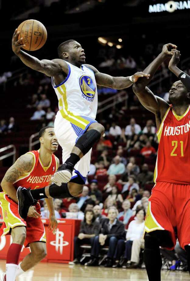 Golden State Warriors' Nate Robinson (2) shoots between Houston Rockets' Courtney Lee (5) and Samuel Dalembert (21) in the first half of an NBA basketball game, Thursday, March 22, 2012, in Houston. (AP Photo/Pat Sullivan) Photo: Pat Sullivan, Associated Press / AP