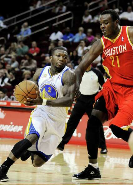Golden State Warriors' Nate Robinson (2) drives around Houston Rockets' Samuel Dalembert (21) in the