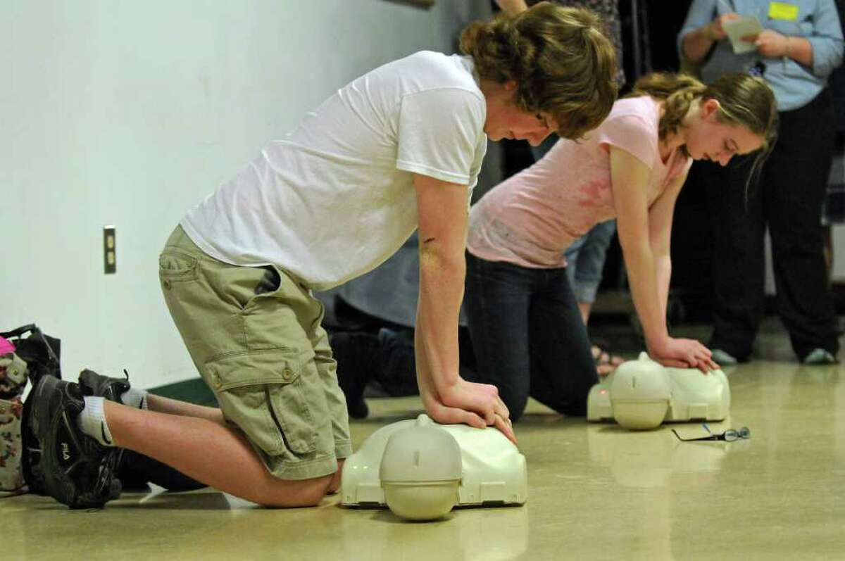 Averill Park High School students Scott Gallerie, 14, left, and Samantha St. Germain, 16, are among 1000 students at the school who have been taught CPR by the Sand Lake Ambulance Company, as they demonstrate CPR at the school on Thursday March 22, 2012 in Averill Park, N.Y. An event was held to promote a CPR in Schools bill, that would guarantee that every high school student in the state would learn CPR. Two local survivors of sudden cardiac arrest who were saved by CPR were in attendance. (Philip Kamrass / Times Union )
