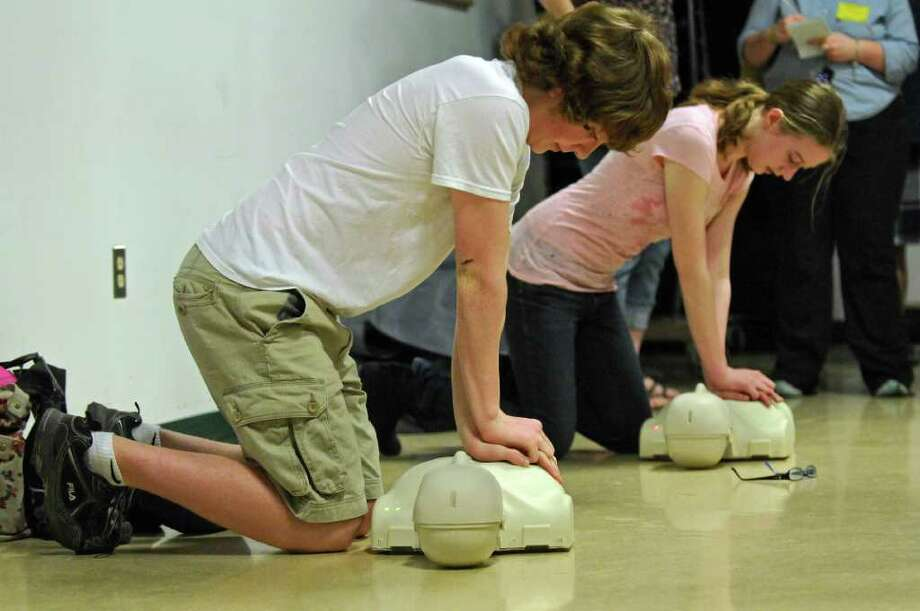 Averill Park High School students Scott Gallerie, 14, left, and Samantha St. Germain, 16, are among 1000 students at the school who have been taught CPR by the Sand Lake Ambulance Company,  as they demonstrate CPR at the school on Thursday March 22, 2012 in Averill Park, N.Y.  An event was held to promote a CPR in Schools bill, that would  guarantee that every high school student in the state would learn CPR. Two local survivors of sudden cardiac arrest who were saved by CPR were in attendance.  (Philip Kamrass / Times Union ) Photo: Philip Kamrass / 00016919A