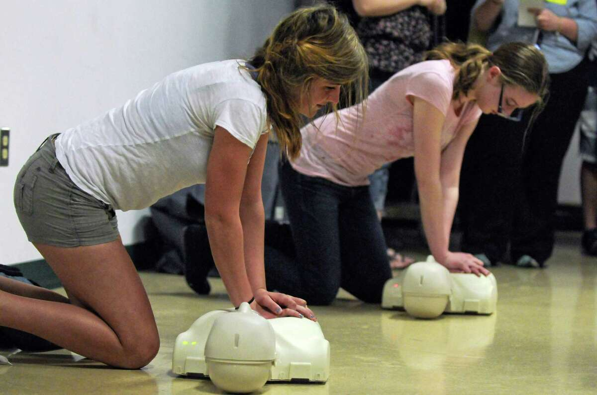 Averill Park High School students Chelsea Morgia, 15, left, and Samantha St. Germain, 16, are among 1000 students at the school who have been taught CPR by the Sand Lake Ambulance Company, as they demonstrate CPR at the school on Thursday March 22, 2012 in Averill Park, N.Y. An event was held to promote a CPR in Schools bill, that would guarantee that every high school student in the state would learn CPR. Two local survivors of sudden cardiac arrest who were saved by CPR were in attendance. (Philip Kamrass / Times Union )