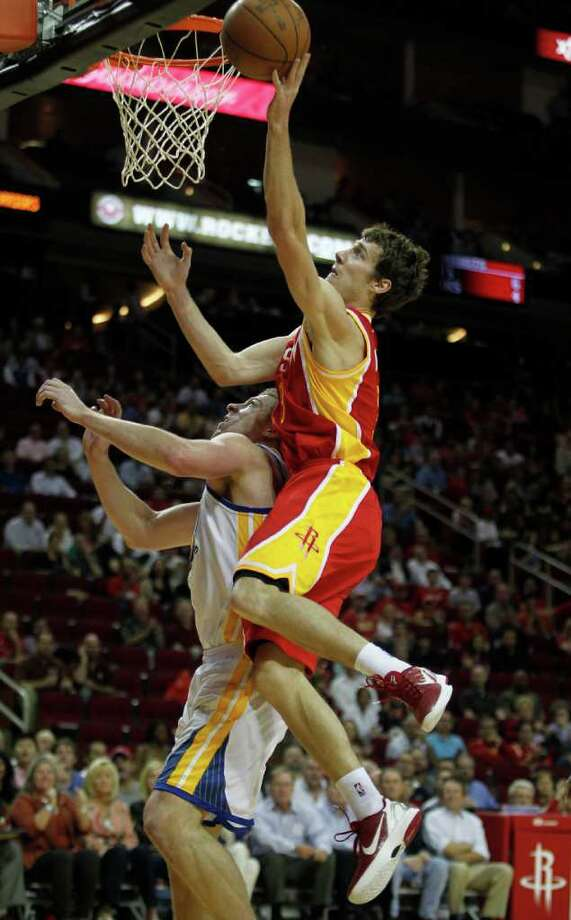 The Houston Rockets Goran Dragic right, shoots the ball over the Golden State Warriors David Lee during the first quarter of NBA game action at the Toyota Center Thursday, March 22, 2012, in Houston. Photo: James Nielsen, Chronicle / © 2012 Houston Chronicle