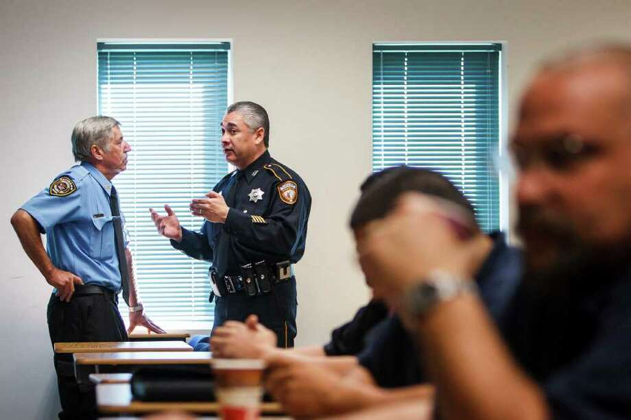 Private security guard Juergen Jaggi, left, talks to Deputy Alfred Gonzales  during an eight-hour training session Thursday at the Harris County Sheriff's Academy in Humble. Photo: Michael Paulsen / © 2012 Houston Chronicle
