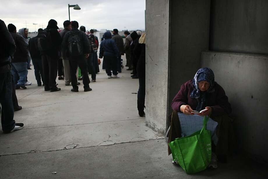 A woman finds cover from the wind while waiting in line for healthcare at the Oakland coliseum in Oakland, Calif., on Thursday, March 22, 2012. Photo: Liz Hafalia, The Chronicle
