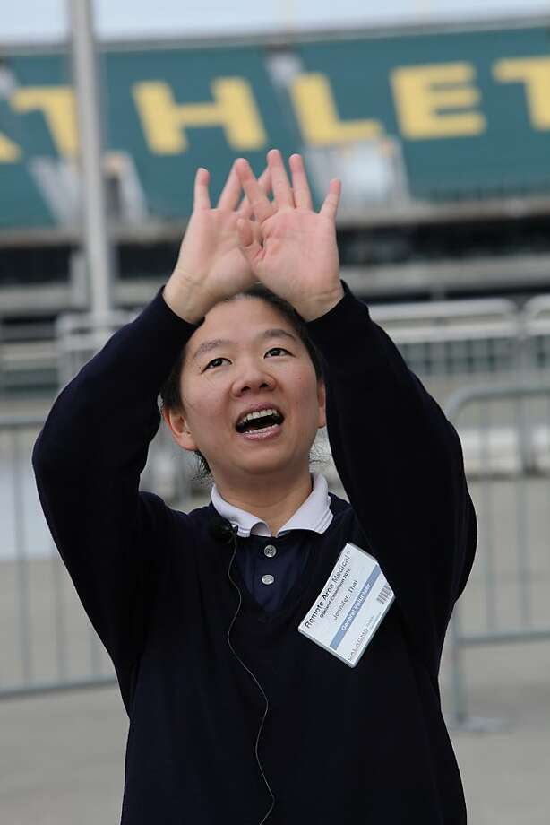 Volunteer Jennifer Thai from the Tzu Chi foundation singing to the line of patients using sign language at the Oakland coliseum in Oakland, Calif., on Thursday, March 22, 2012. Photo: Liz Hafalia, The Chronicle