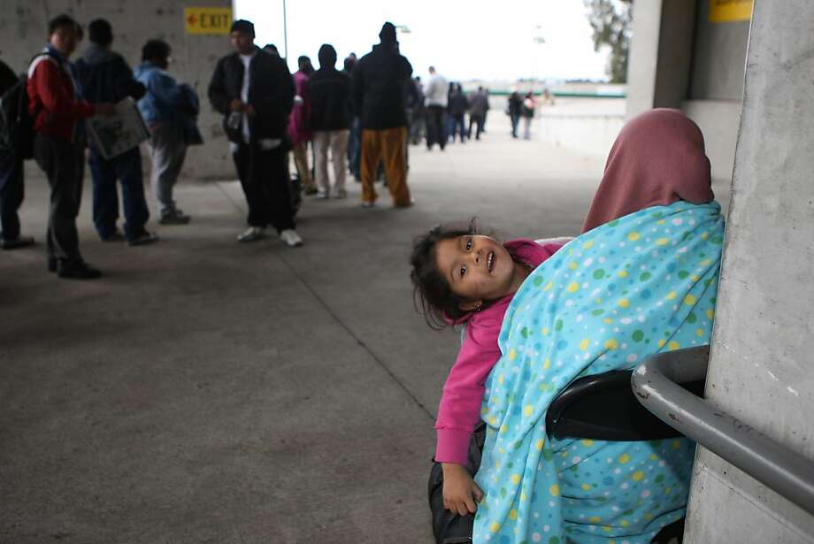 Four year old Jasmine Gastelum (middle) from Richmond at the Oakland coliseum in Oakland, Calif., while waiting with her mother Griselda Gastelum while her dad waits in line for them to receive health care on Thursday, March 22, 2012. Photo: Liz Hafalia, The Chronicle