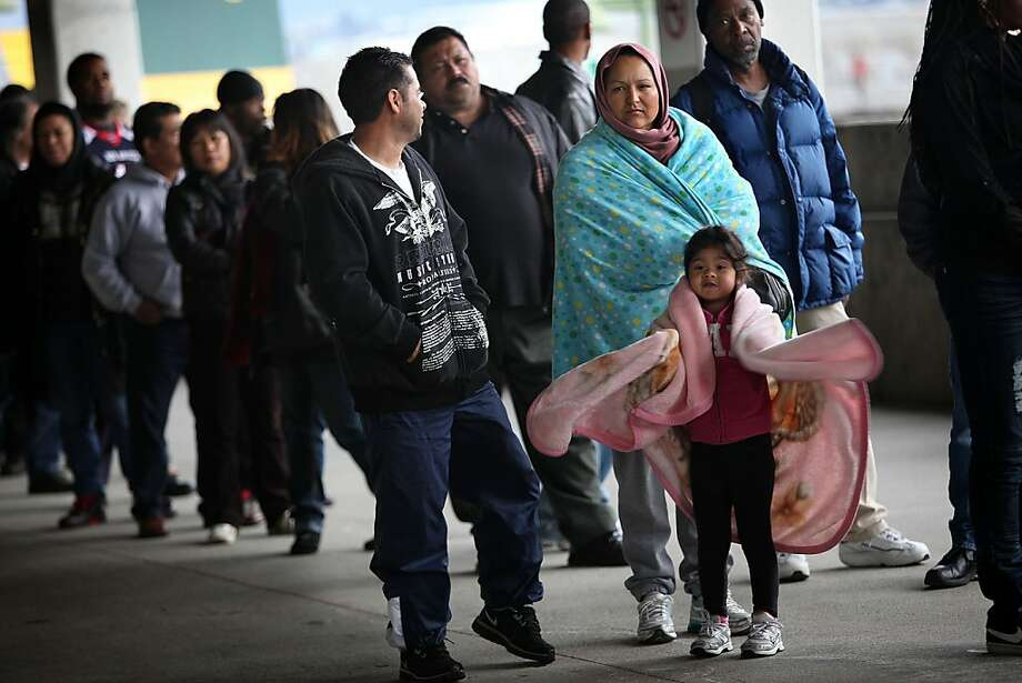 Four year old Jasmine Gastelum (middle) from Richmond at the Oakland coliseum in Oakland, Calif.,  waiting with her mother Griselda Gastelum (blue blanket) with her dad Hector Gastelum (left) to receive health care on Thursday, March 22, 2012. Photo: Liz Hafalia, The Chronicle