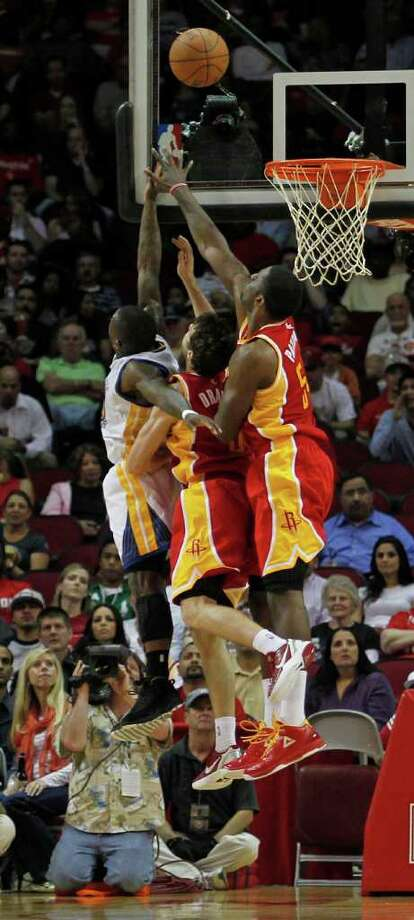 The Golden State Warriors Brandon Rush left, the Houston Rockets Goran Dragic center and Patrick Patterson jump for a rebound during the second quarter of NBA game action at the Toyota Center Thursday, March 22, 2012, in Houston. Photo: James Nielsen, Chronicle / © 2012 Houston Chronicle