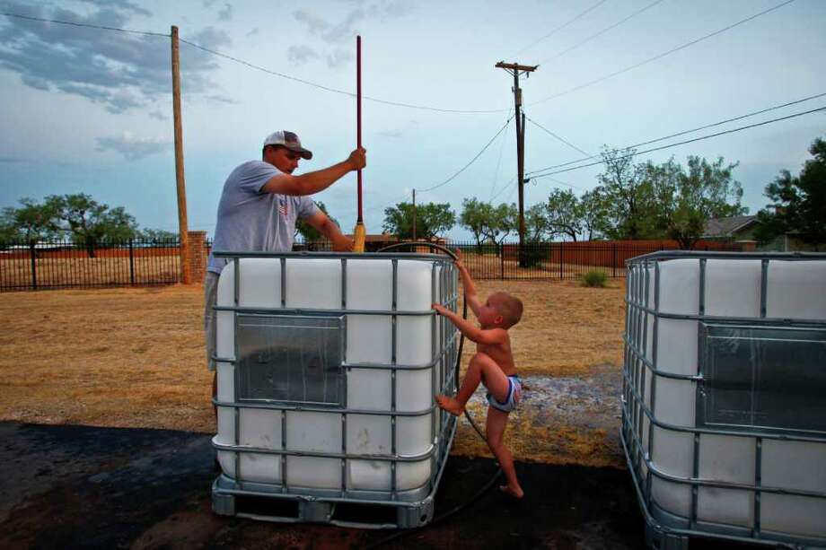 Brennen Hood, 3, tries to help his father, Aaron Hood, school superintendent and athletic director for Robert Lee High School, clean chemical containers to haul water for the school's football fields during the drought last summer. Photo: Michael Paulsen / © 2011 Houston Chronicle