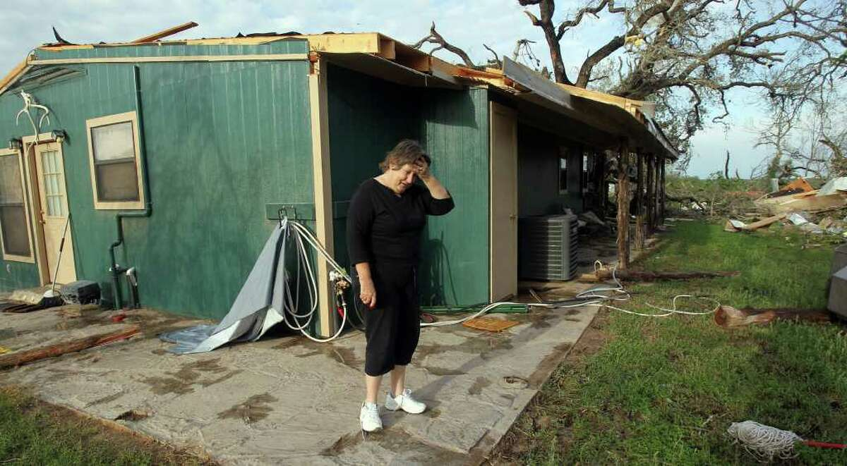 Donna Littleton pauses while looking over the damage that took place at her home Monday night March 20, 2012 on private road 6744 between Lytle and Natalia, Texas. Littleton was at home with her husband James Littleton when she said they heard a loud swirling noise and got into their bath tub for shelter.