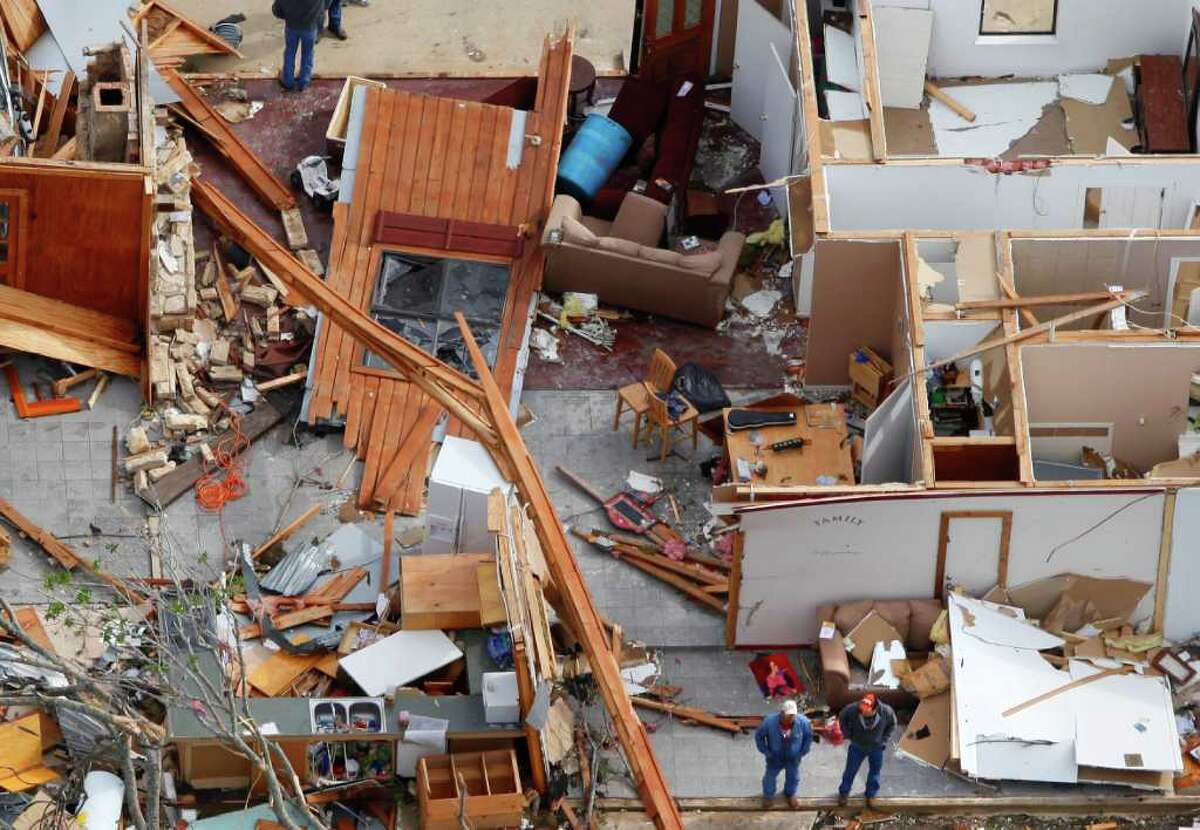 Two men stand (bottom center of image) in the remains of a house damaged from an overnight tornado in the Devine area, as seen in this Tuesday March 20, 2012 aerial image.