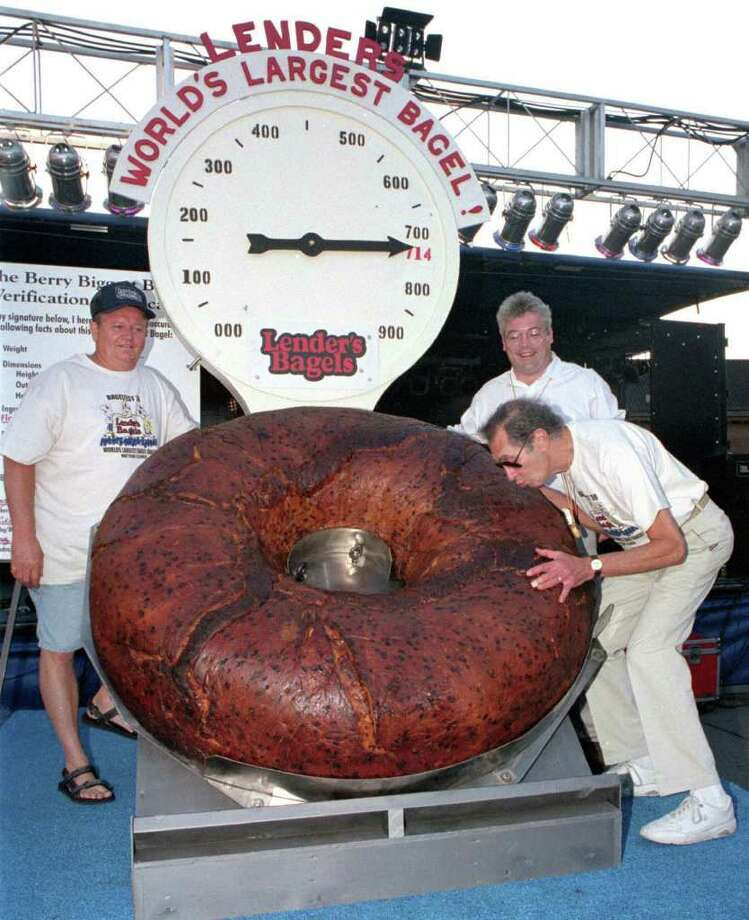 FILE - In this July 24, 1998 photo, Murray Lender kisses the world's largest bagel while baker Larry Wilkerson, left, and Lender's Bagel Bakery manager Jim Cudahy watch after the weight of the bagel was revealed during Bagelfest in Mattoon, Ill.  Murray Lender, who helped turn his father's small Connecticut bakery into a national company that introduced bagels to many Americans for the first time, has died in Florida. He was 81. Lender's wife, Gillie Lender, tells The Associated Press that her husband died Wednesday, March 21, 2012 at a hospital in Miami from complications from a fall he suffered 10 weeks ago. The couple lived in both Aventura, Fla., and Woodbridge, Conn.  (AP Photo/Journal Gazette, Doug Lawhead) Photo: DOUG LAWHEAD