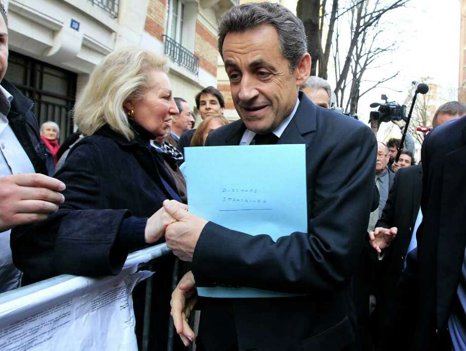 French President Nicolas Sarkozy, right, shakes hands with supporters near his campaign party headquarters, Paris, Thursday, March 22, 2012. Sarkozy said Thursday an investigation was under way to see if the suspect in a series of radical Islam-inspired killings had any accomplices. (AP Photo/Jacques Brinon) Photo: Jacques Brinon / AP