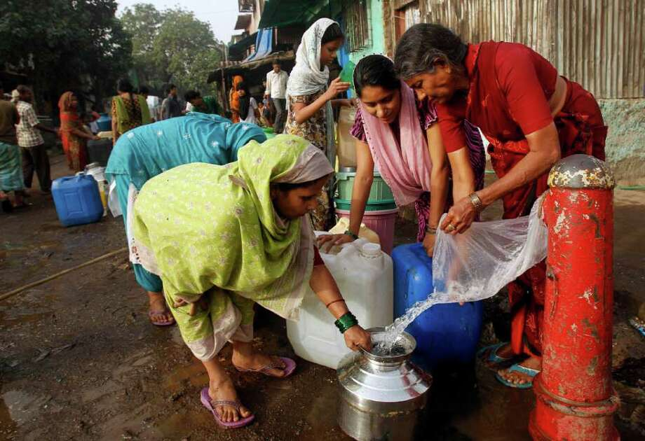 Indian women collect water from a broken pipe in a slum on the outskirts of Mumbai, India, Thursday, March 22, 2012. The U.N. estimates that more than one in six people worldwide do not have access to 20-50 liters (5-13 gallons) of safe freshwater a day to ensure their basic needs for drinking, cooking and cleaning. (AP Photo/Rafiq Maqbool) Photo: Rafiq Maqbool