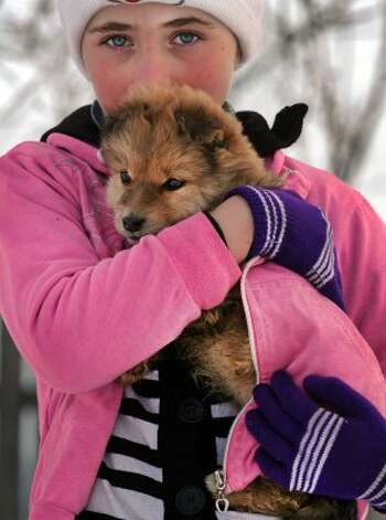 A girl holds her puppy to keep it warm on February 15, 2012 outside the village of Pitulicea, 100 kms east of Bucharest.  (DANIEL MIHAILESCU / AFP/Getty Images)