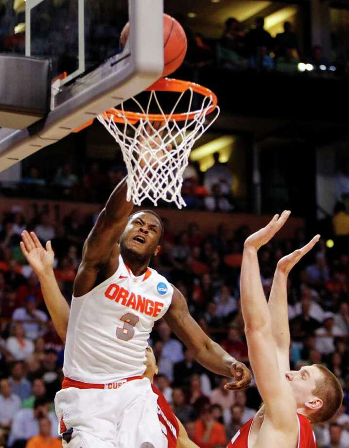Syracuse guard Dion Waiters (3) shoots past Wisconsin's Jared Berggren (40) in the second half of an East Regional semifinal game in the NCAA men's college basketball tournament, Thursday, March 22, 2012, in Boston. Syracuse won 64-63. (AP Photo/Michael Dwyer) Photo: Michael Dwyer