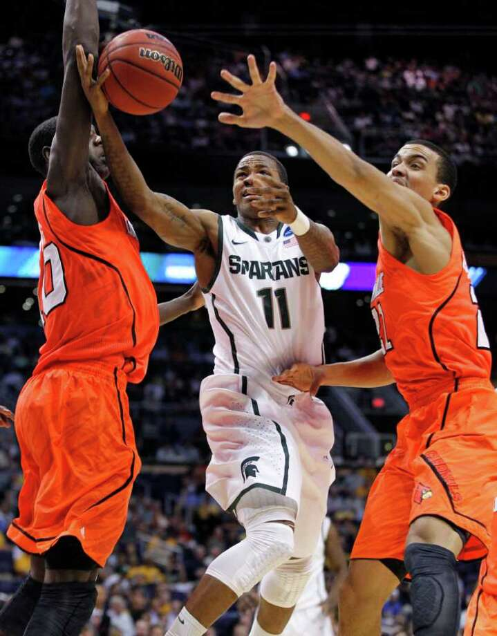 Michigan State's Keith Appling (11) drives between Louisville defenders Gorgui Dieng, left, and Elisha Justice during the first half of an NCAA men's college basketball tournament West Regional semifinal on Thursday, March 22, 2012, in Phoenix. (AP Photo/Chris Carlson) Photo: Chris Carlson