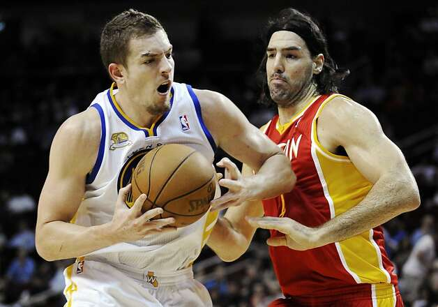 Golden State Warriors' David Lee, left, drives against Houston Rockets' Luis Scola in the first half of an NBA basketball game, Thursday, March 22, 2012, in Houston. Photo: Pat Sullivan, Associated Press