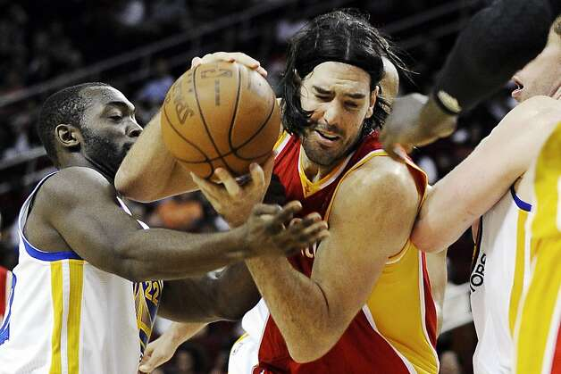 Houston Rockets' Luis Scola, center, pushes through between Golden State Warriors' Charles Jenkins (22) and David Lee, right, in the second half of an NBA basketball game, Thursday, March 22, 2012, in Houston. The Rockets won 109-83. Photo: Pat Sullivan, Associated Press