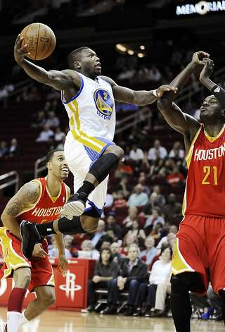 Golden State Warriors' Nate Robinson (2) shoots between Houston Rockets' Courtney Lee (5) and Samuel Dalembert (21) in the first half of an NBA basketball game, Thursday, March 22, 2012, in Houston. Photo: Pat Sullivan, Associated Press