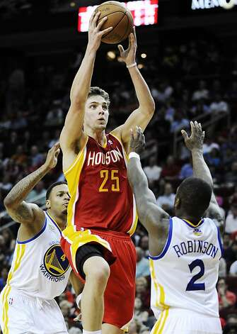 Houston Rockets' Chandler Parsons (25) shoots between Golden State Warriors' Brandon Rush (4) and Nate Robinson (2) in the second half of an NBA basketball game, Thursday, March 22, 2012, in Houston. The Rockets won 109-83. Photo: Pat Sullivan, Associated Press