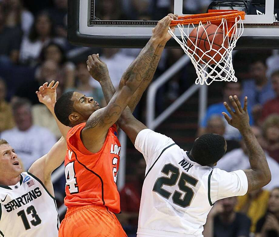 Louisville's Chane Behanan, center, dunks against Michigan State's Derrick Nix (25) as Michigan State's Austin Thornton (13) looks on during the second half of an NCAA men's college basketball tournament West Regional semifinal on Thursday, March 22, 2012, in Phoenix. (AP Photo/Matt York) Photo: Matt York, Associated Press
